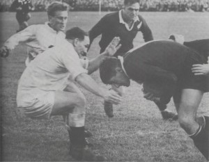 Colin Meads decides to barge through Judd rather than seek a way round him. English half-back, Simon Clarke, and All Black prop, Ian Clarke, close in.