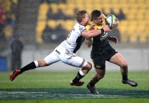 TJ Perenara of the Hurricanes (R) is tackled by Michael Claassens of the Sharks during the Super Rugby quarter-final match between South Africa's Coastal Sharks and New Zealand's Wellington Hurricanes at Westpac Stadium in Wellington on July 23, 2016. / AFP / MARTIN HUNTER (Photo credit should read MARTIN HUNTER/AFP/Getty Images)