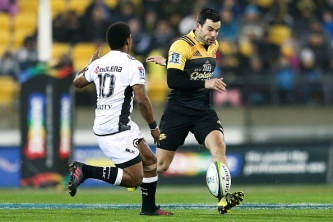 WELLINGTON, NEW ZEALAND - JULY 23: James Marshall of the Hurricanes kicks past Garth April of the Sharks during the Super Rugby Quarterfinal match between the Hurricanes and the Sharks at Westpac Stadium on July 23, 2016 in Wellington, New Zealand. (Photo by Hagen Hopkins/Getty Images)